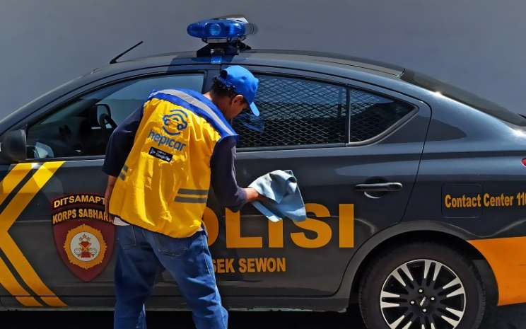 Pencuci mobil mitra HEPICAR mengerjakan pencucian mobil patroli polisi dalam program sosial di Yogyakarta. - istimewa