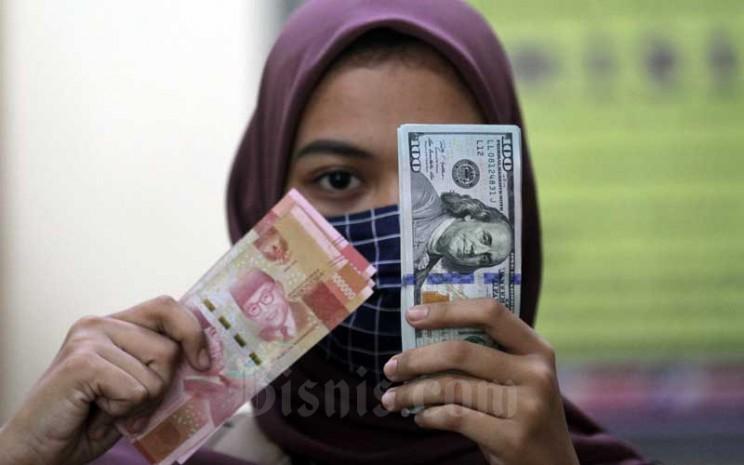 Karyawati menunjukan uang Rupiah dan dolar AS di salah satu gerai penukaran mata uang asing di Jakarta, Minggu (7/6/2020). Bisnis - Arief Hermawan P