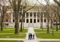 Pejalan kaki berjalan di dalam kampus Harvard University di Cambridge, Massachusetts, AS, Senin (20/4/2020)./Bloomberg-Adam Glanzman