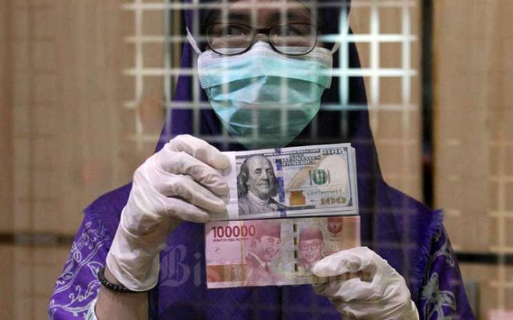 Karyawati menunjukan mata uang Rupiah dan Dollar Ameika Serikat di salah satu gerai penukaran mata uang asing di Jakarta, Kamis (2/4/2020). Bisnis - Arief Hermawan P