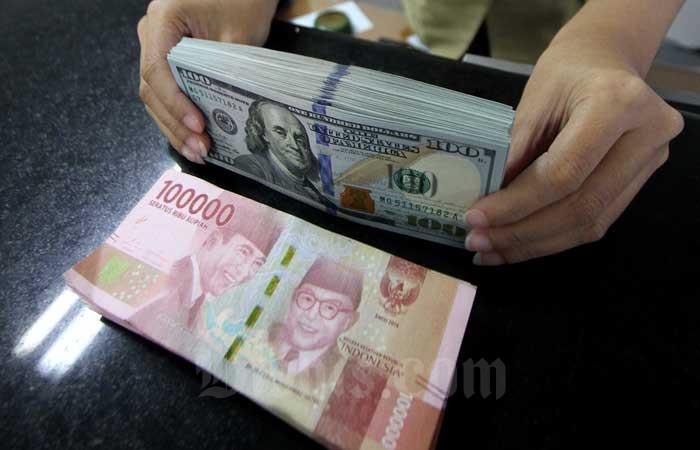 Karyawan menghitung uang di salah satu gerai penukaran uang di Jakarta, Senin (3/2/2020). PT Pemeringkat Efek Indonesia (Pefindo) mengakui terjadi peningkatan profil risiko di pasar surat utang korporasi akibat dampak Covid-19. Bisnis - Arief Hermawan P