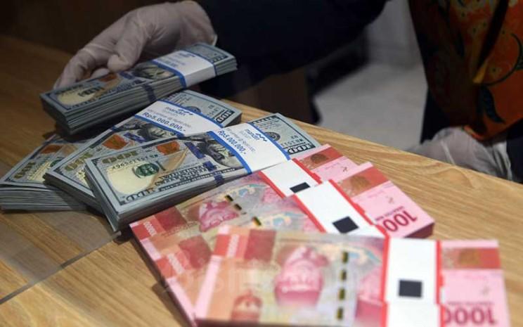 Pegawai bank menata uang dolar di kantor cabang bank Mandiri Syariah di Jakarta, Senin (20/4/2020). Tren besaran nilai emisi penerbitan obligasi korporasi diyakini bakal meningkat di semester II/2020 seiring dengan membaiknya pasar, baik dari sisi cost of fund maupun potensi penyerapan. Bisnis - Abdurachman