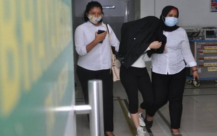 Personel kepolisian membawa artis berinisial H (tengah) saat menjalani pemeriksaan kesehatan di Rumah Sakit Bhayangkara Polda Sumut, Medan, Sumatra Utara, Senin (13/7/2020). H yang merupakan selebgram dan artis Film Televisi (FTV) tersebut ditangkap Polrestabes Medan dari sebuah hotel yang diduga terlibat dalam kasus prostitusi. ANTARA FOTO - Septianda Perdana