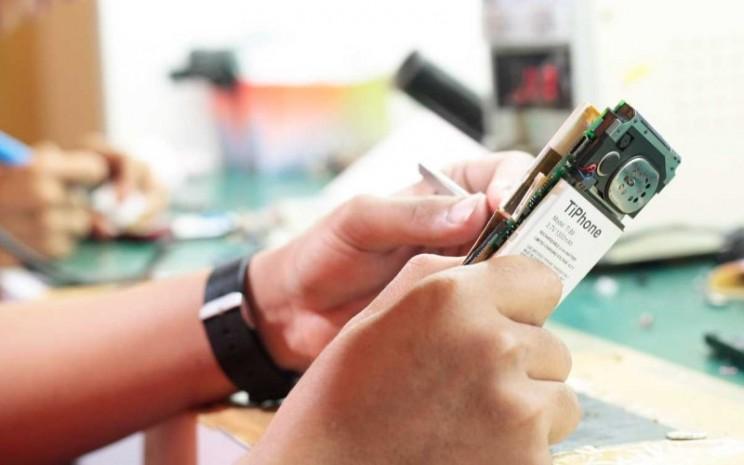 Seorang teknisi tengah memperbaiki telepon selular. Usaha service center adalah salah satu pilar bisnis PT Tiphone Mobile Indonesia Tbk. - tiphone.co.id