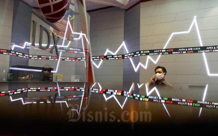 Pengunjung melintas di dekat papan layar elektronik yang menampilkan pergerakan Indeks Harga Saham Gabungan (IHSG) di Bursa Efek Indonesia (BEI), Jakarta, Senin (22/6/2020). Bisnis - Eusebio Chrysnamurti