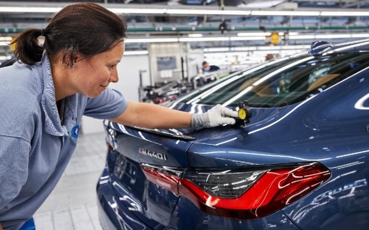 Sentuhan akhir pada BMW Seri 4 Coup sebelum keluar dari jalur perakitan di Pabrik Dingolfing. Selain dari segi produk yang semakin lengkap, BMW juga diuntungkan dengan peluncuran mobil-mobil baru edisi terbatas. Inovasi penjualan dari produsen asal Jerman itu juga menjadi faktor pendorong kinerja penjualan.  - BMW