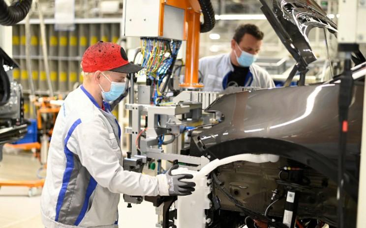 Dua karyawan Volkswagen di pabrik Zwickau memasang lampu depan pada ID.3. Pabrik ini beroperasi kembali sejak 27 April 2020 dengan menerapkan protokol kesehatan, seperti pemakaian penutup mulut/hidung di tempat kerja dengan jarak antarpekerja kurang dari 1,5 meter.