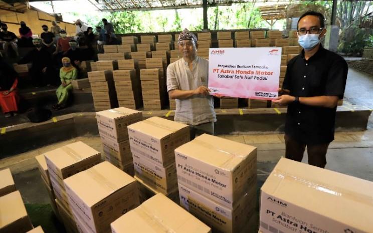 GM Corporate Communication AHM Ahmad Muhibbuddin (kanan) secara simbolis menyerahkan bantuan paket sembako kepada para pekerja seni yang diwakili oleh Pimpinan Saung Angklung Udjo Taufik Hidayat Udjo (20/7 - 2020). AHM