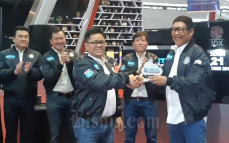 Direktur Utama Digital Mediatama Maxima Budiasto Kusuma menyerahkan cindera mata kepada Direktur Utama Bursa Efek Indonesia Inarno Djajadi setelah resmi mencatatkan saham perseroan dengan kode DMMX di Mainhall BEI, Senin (21/10/2019). - Bisnis - Dwi Nicken Tari