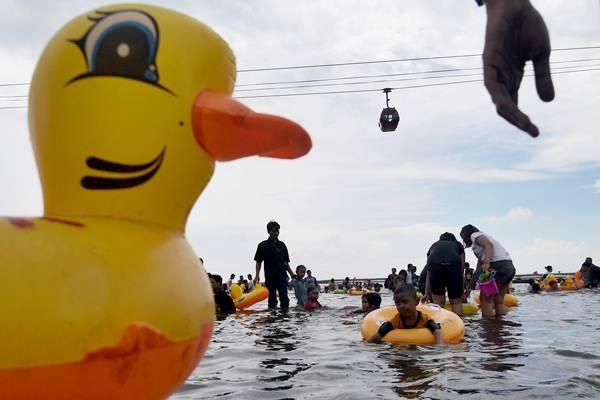 Pengunjung bermain di pantai Ancol, Jakarta, Senin (26/6). - Antara/Sigid Kurniawan