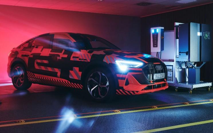 Audi e-tron. Pengisian dua arah di rumah yang juga dikenal sebagai vehicle to home (V2H) ini memiliki potensi besar untuk mengurangi biaya listrik pemilik rumah dan meningkatkan stabilitas jaringan. - AUDI