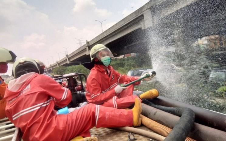 Petugas Suku Dinas Penanggulangan Kebakaran dan Penyelamatan Jakarta Timur menyemprot disinfektan di sejumlah jalan protokol di Jatinegara, Senin (13/4/2020). - Antara