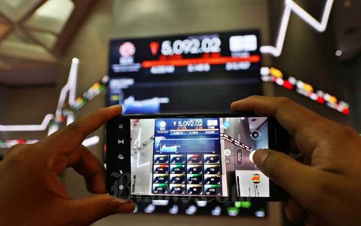 Pengunjung memotret papan elektronik yang menampilkan pergerakan Indeks Harga Saham Gabungan (IHSG) di Bursa Efek Indonesia, Jakarta, Jumat (17/7/2020). Bisnis - Eusebio Chrysnamurti