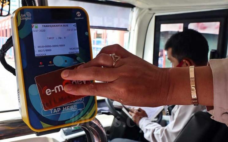 Penumpang melakukan tapping saat menaiki bus listrik Transjakarta di Terminal Blok M, Jakarta, Senin (13/7/2020). Bisnis - Eusebio Chrysnamurti