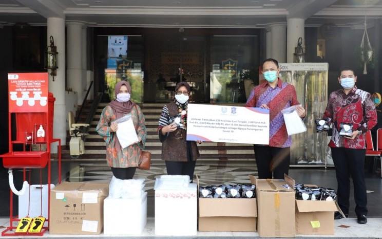 Zulfakar Ali, Kepala Fasilitas Produksi Unilever Surabaya menyerahkan bantuan kemanusiaan penanggulangan pandemi Covid/19 berupa 15.000 unit barang bantuan yang diterima oleh Walikota Surabaya Tri Rismaharini. Istimewa