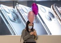 Warga Hong Kong menggunakan ponselnya di depan papan iklan iPhone buatan Apple Inc. di Hong Kong, China, Jumat (14/2/2020)./Bloomberg-Justin Chin
