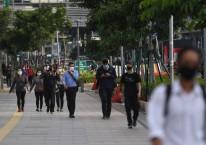 Sejumlah pekerja berjalan usai bekerja dengan latar belakang gedung perkantoran di Jl. Jenderal Sudirman, Jakarta, Kamis (16/4/2020)./ANTARA FOTO-Akbar Nugroho Gumay