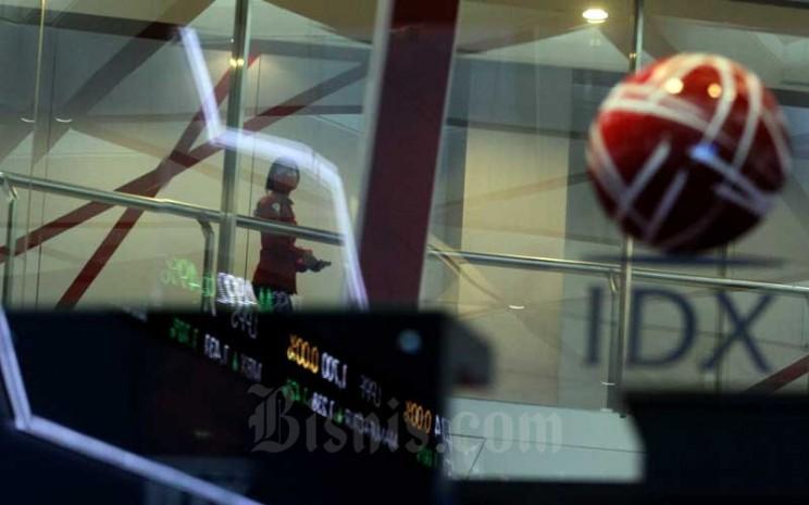 Karyawan melintas di dekat layar elektronik yang menampilkan pergerakan Indeks Harga Saham Gabungan (IHSG) di PT Bursa Efek Indonesia (BEI), Jakarta, Selasa (9/6/2020). Bisnis - Arief Hermawan P