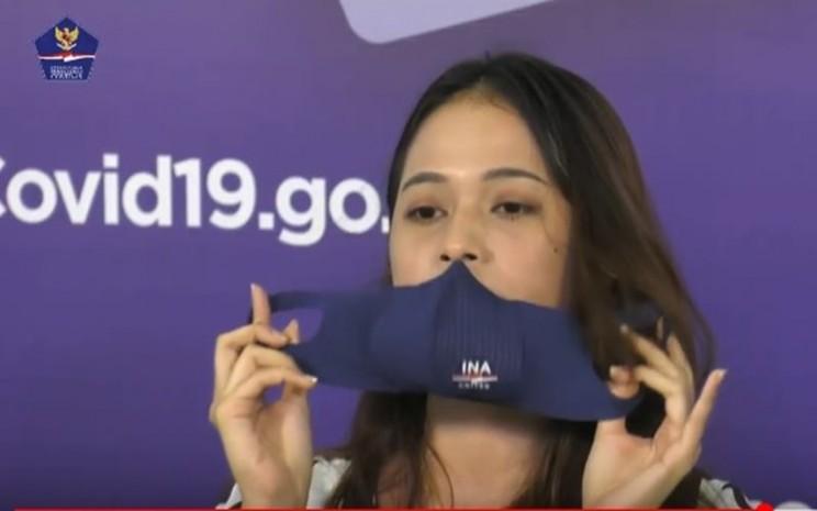 Ilustrasi-Anggota Tim Pakar Satgas Covid-19 Shela Rachmayanti mempraktikkan cara melepas masker yang benar./JIBI - Bisnis/Nancy Junita