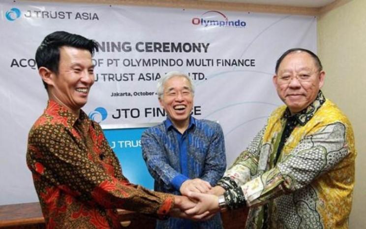 Wakil Presiden Direktur J Trust Olympindo Multi Finance Teruhiko Miwa (kiri) Komisaris Utama Olympindo Multi Finance (OMF) Ang Andi Bintoro (kanan), dan Direktur J Trust Asia (JTA), Nobiru Adachi berpose usai penandatanganan akuisisi 60 persen saham OMF oleh J Trust Asia di Jakarta, Kamis (4/10/2018). - jto.co.id