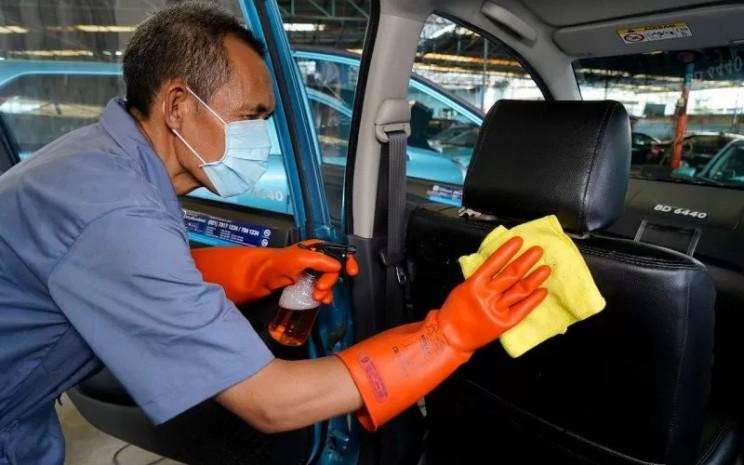 Ilustrasi pengemudi tengah membersihkan kabin mobil Bluebird.  - Bluebird/Antara