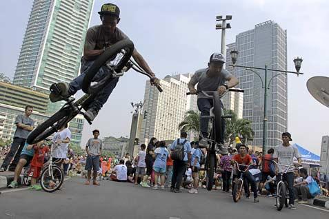 Pesepeda BMX beratraksi di kawasan Bunderan HI, Jakarta, Minggu (21/9/2014). Olahraga yang termasuk dalam olahraga ekstrem tersebut kembali digandrungi sejumlah remaja Ibu Kota.  - ANTARA