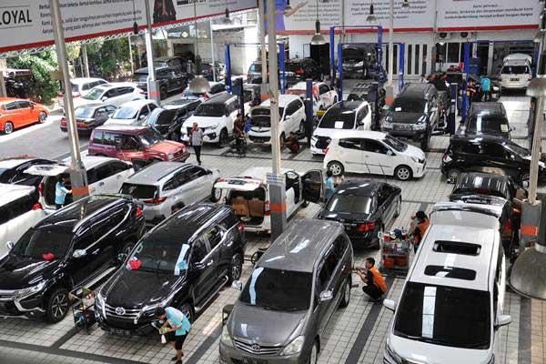 Montir memperbaiki mobil milik pelanggan di Medan, Sumatra Utara, Kamis (3/1/2019). - ANTARA/Septianda Perdana