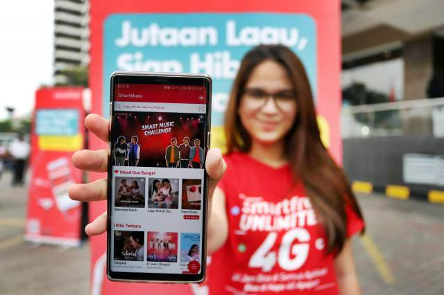 Model memperlihatkan aplikasi khusus streaming musik dari Smartfren yaitu SmartMusic saat peluncurannya di Jakarta, Minggu (10/2/2019). - Bisnis/Abdullah Azzam