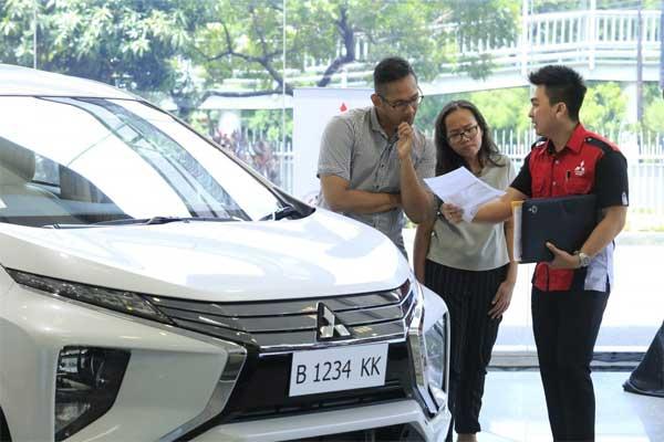 Wiraniaga sedang menjelaskan produk kendaraan Mitsubishi kepada calon konsumen.  - mitsubishi