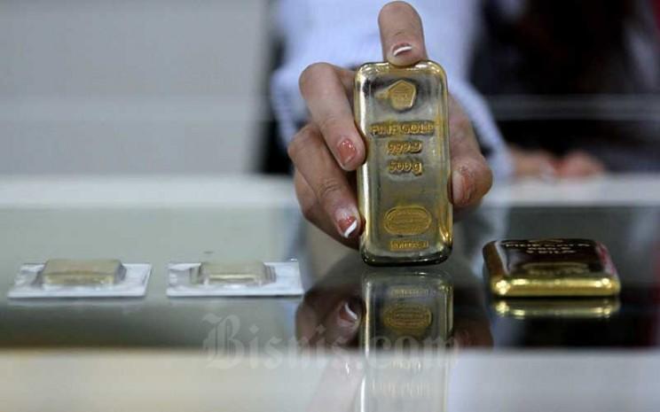 Karyawati menunjukkan replika logam mulia di Butik Emas Antam, Jakarta, Kamis (6/8/2020). Bisnis - Arief Hermawan P