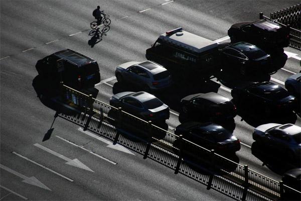 Seorang pengendara sepeda melintas di depan mobil yang menunggu di lampu lalu lintas di Beijing, China 29 Oktober 2018.  - REUTERS