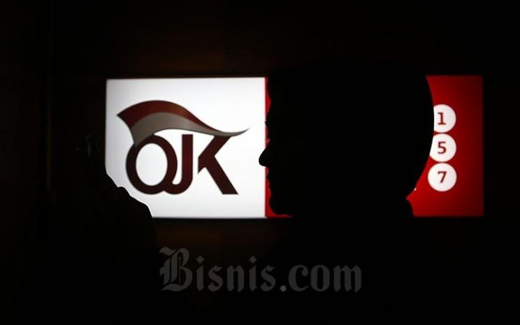 Karyawan berada di dekat logo Otoritas Jasa Keuangan di Jakarta, Jumat (17/1/2020). Bisnis - Abdullah Azzam