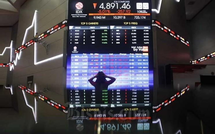 Karyawan beraktifitas di dekat layar pergerakan Indeks Harga Saham Gabungan (IHSG) di Bursa Efek Indonesia, Jakarta, Kamis (10/9/2020).  Bisnis - Himawan L Nugraha