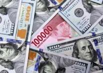 Karyawati menunjukan uang Rupiah dan dolar AS di salah satu gerai penukaran mata uang asing di Jakarta, Minggu (7/6/2020)./Bisnis-Arief Hermawan P
