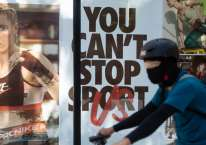 Seorang pesepeda melewati gerai Nike di Bonifacio Global City, Metro Manila, Filipina, Senin (27/7/2020)./Bloomberg-Geric Cruz