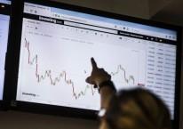 Seorang siswa menunjuk ke monitor yang menampilkan harga BitCoin terhadap dolar AS melalui portal untuk perdagangan mata uang virtual. Carlos Becerra / Bloomberg