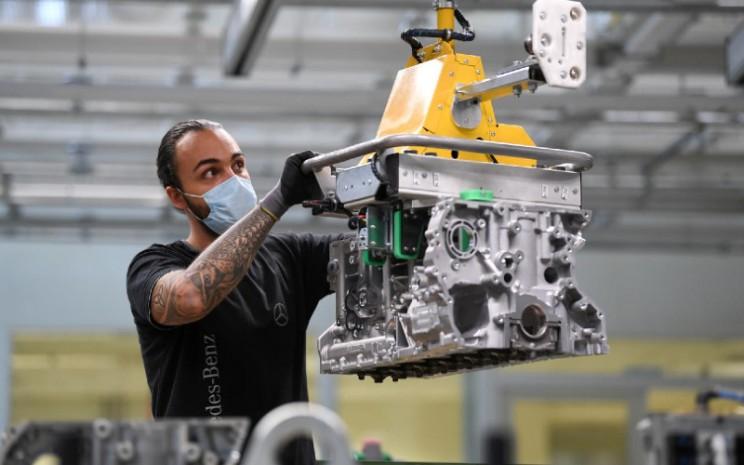 Seorang pekerja merakit mesin untuk model Mercedes/Benz S di pabrik Mesin Daimler di Bad Cannstatt, ketika penyebaran virus corona (Covid/19) berlanjut di dekat Stuttgart, Jerman, 22 April 2020. / REUTERS