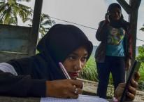 Siswa kelas IX Sekolah Menengah Pertama (SMP) Plus Pasawahan mengerjakan tugas sekolah di pos kamling Desa Pasawahan, Kabupaten Ciamis, Jawa Barat, Kamis, (16/7/2020). Pelajar yang tinggal di desa terpecil terpaksa mengerjakan tugas sekolah di luar rumah lantaran keterbatasan jaringan internet sedangkan sekolah hanya bisa memfasilitasi kegiatan belajar mengajar (KBM) secara daring mengunakan aplikasi WhatsApp Grup serta Facebook Messenger. ANTARA FOTO/Adeng Bustomi