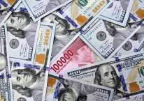 Karyawati menunjukan uang Rupiah dan dolar AS di salah satu gerai penukaran mata uang asing di Jakarta, Minggu (7/6/2020). Bisnis/Arief Hermawan P