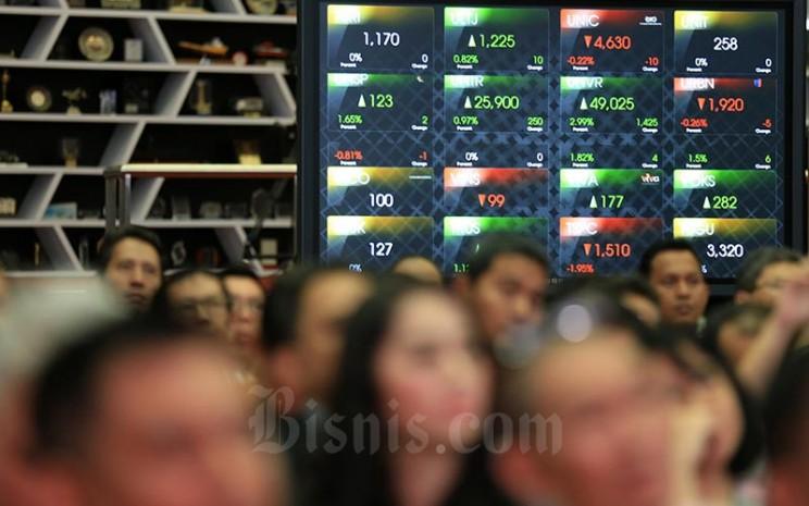 Karyawan berada di dekat monito pergerakan Indeks Harga Saham Gabungan (IHSG) di Bursa Efek Indonesia, Jakarta, Selasa (30/1). Bisnis - Nurul Hidayat