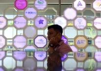 Karyawan berkomunikasi didekat logo beberapa perusahaan asuransi di kantor Asosiasi Asuransi Jiwa Indonesia (AAJI) di Jakarta, Selasa (15/1/2020). Bisnis/Nurul Hidayat