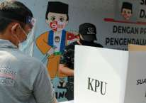 Petugas Kelompok Penyelenggara Pemungutan Suara (KPPS) dengan menggunakan alat pelindung diri (APD) mengawasi pemilih di bilik suara khusus saat simulasi pemungutan suara dengan protokol kesehatan pencegahan dan pengendalian COVID-19 di TPS 18 Cilenggang, Serpong, Tangerang Selatan, Banten, Sabtu (12/9/2020). ANTARA FOTO/Muhammad Iqbal/pra