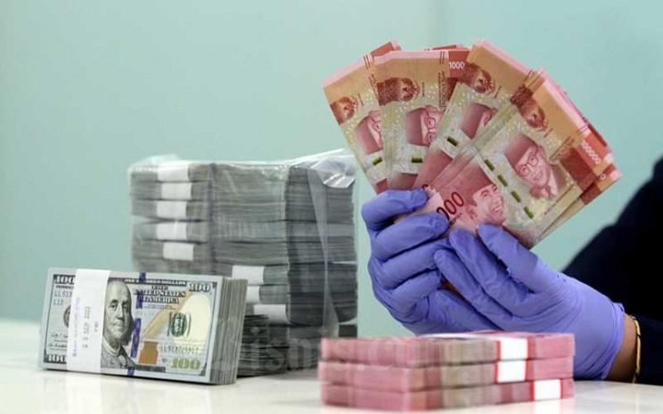 Karyawati menghitung uang rupiah dan dollar AS di salah satu bank di Jakarta, Kamis (10/9/2020). Bisnis - Arief Hermawan P