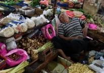 Pedagang aneka bahan bumbu masakan tertidur saat menunggu calon pembeli di Pasar Minggu, Jakarta Selatan, Senin (27/1/2020)./ ANTARA - Sigid Kurniawan