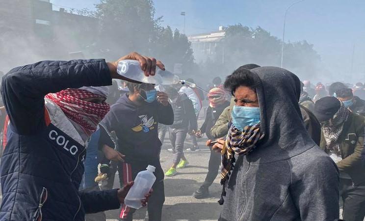 Seorang pria menuangkan cairan medis di hadapan seorang demonstran yang terkena dampak gas air mata selama berlangsungnya protes anti-pemerintah di Nassiriya, Irak 26 Januari 2020. - Reuters
