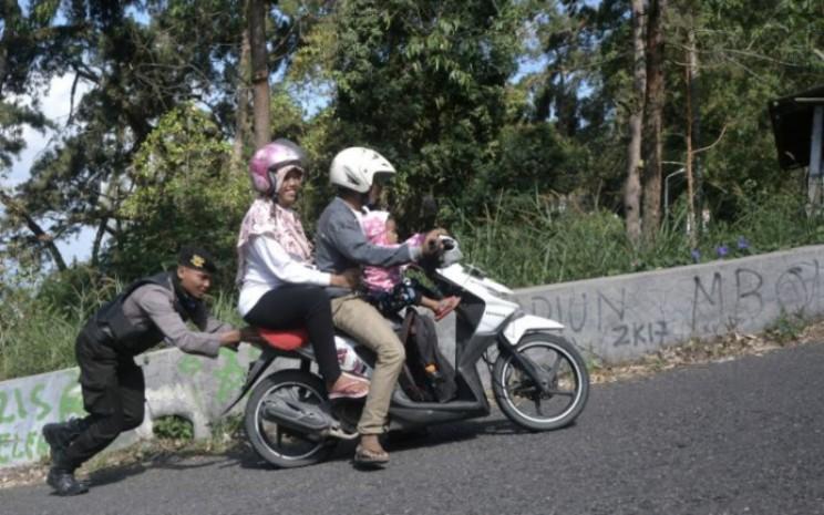 Polisi mendorong sepeda motor warga. Saat motor injeksi kehabisan bensin, pengguna bisa menepi dan cari pom bensin terdekat. Selain itu, hindari langsung menghidupkan motor setelah diisi.  - ANTARA
