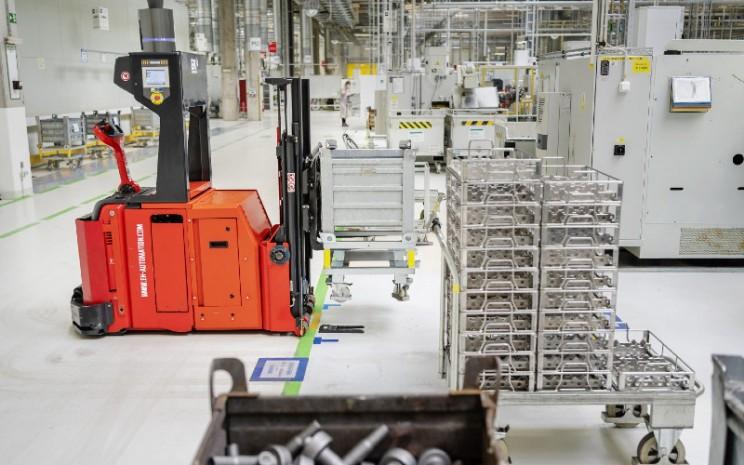 Komponen otomatis dipasok ke jalur pemrosesan CNC dalam produksi.  - SKoda