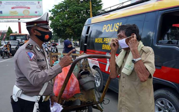 Petugas Satuan Lalu Lintas Polres Sorong Kota (kiri) mengingatkan pentingnya penggunaan masker kepada warga di Kota Sorong, Papua Barat, Kamis (10/9/2020). Kasus COVID-19 di Papua Barat terus meningkat, data per Kamis (10/9) jumlah kasus positif di Papua Barat tercatat 970 orang, sembuh 649 orang dan meninggal 17 orang. ANTARA FOTO - Olha Mulalinda