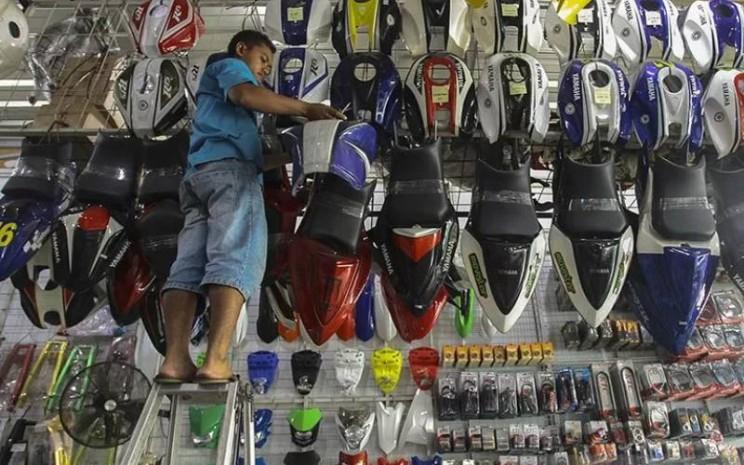 Pedagang menata dagangan berupa aksesori modifikasi motor di tokonya di kawasan Otista, Jakarta. /ANTARA