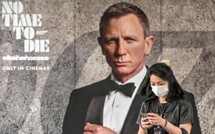 Warga melintas di depan poster film James Bond No Time to Die - Bloomberg